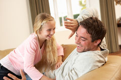 Young father with girl having fun on sofa Stock Image
