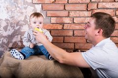 Young father gives his son an green apple to eat. On a red bricks wall  background. One year baby in jeans sitting royalty free stock photo