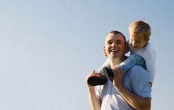Young father giving his son a piggy back ride. As the youngster sits on his shoulders laughing with enjoyment, low angle against a blue sky with copyspace royalty free stock photography