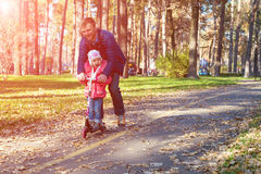 Young Father and Happy Child Riding Kick Scooter in Park Royalty Free Stock Photo