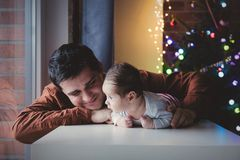 Young father help to a little child lie down on tummy. In first time. Indoor image with focus on infant stock photos
