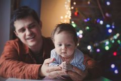 Young father help to a little child lie down on tummy. In first time. Indoor image with focus on infant stock photography