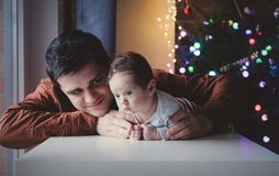 Young father help to a little child lie down on tummy. In first time. Indoor image with focus on infant royalty free stock photo