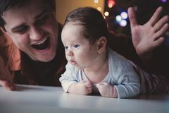 Young father help to a little child lie down on tummy. In first time. Indoor image with focus on infant stock images