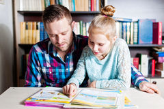 Young father helping her daughter with school project at home. Young father helping her daughter with her school project at home or library stock photos