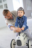 Young father helping his boy child with new toy car. Man helping little boy on a riding toy royalty free stock image