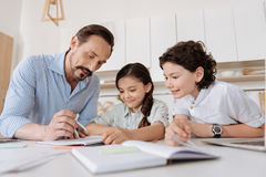 Young father helping his children with math assignments. Listening attentively. Handsome bearded father helping his children to do math assignments via Royalty Free Stock Images