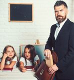 Young father helping his daughters with school project at home. man put book in bag. stock photos