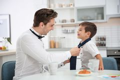 Young father helping his little son to knot necktie. At home stock photos