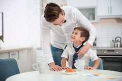 Young father helping his little son to knot necktie. At home royalty free stock photos