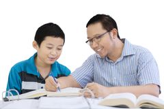 Young father helping his son doing homework. Image of young father helping his son doing homework while sitting in the studio, isolated on white background royalty free stock photos