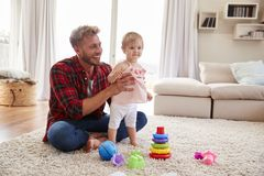 Young father helping toddler daughter stand in sitting room royalty free stock photos