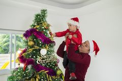 Father helps his son decorating Christmas tree. Young father helps his son decorating a Christmas tree while wearing Christmas hat at home stock photography