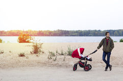 Young father helps mother, he walks with a baby carriage in the Royalty Free Stock Photos