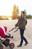 Young father helps mother, he walks with a baby carriage in the Royalty Free Stock Images