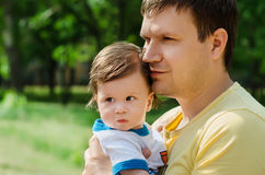 Young father with her baby. Happy young father with her baby looking off into distance in the park Stock Photography