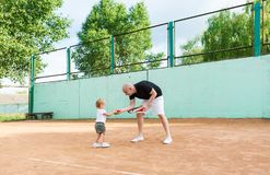 Young father with her little daughter playing on the tennis court. stock photo