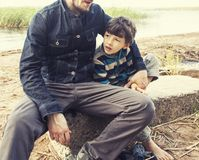 Young father hipster with a beard and his little son on the lake. Shore. Talking, teaching, having fun happy time. Lifestyle people concept close up Stock Images