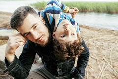 Young father hipster with a beard and his little son on the lake shore. Talking, teaching, having fun happy time Royalty Free Stock Images