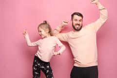 Young father with his baby daughter. Dancing at studio pink background Royalty Free Stock Photography