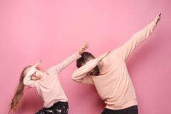Young father with his baby daughter. Dancing at studio pink background Royalty Free Stock Image