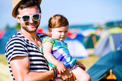 Young father with his baby daughter between tents, summer Royalty Free Stock Images