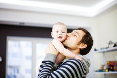 Young father and his baby. Happy family at home, father kiss his son Royalty Free Stock Photography