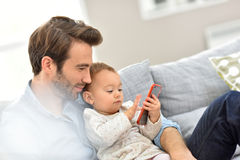 Young father with his baby playing with smartphone Royalty Free Stock Photo