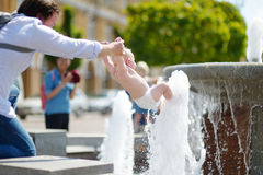 Young father and his baby son by a city fountain Royalty Free Stock Images