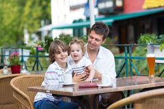 Young father with his children in outside cafe. Young father enjoying a meal with his son and baby daughter in an outside cafe on a nice summer day Stock Image