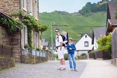 Young father with his children in small German village. Young father hiking with his son and baby daughter in a traditional small German village next to a vine Royalty Free Stock Photos
