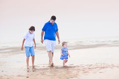 Young father with his children walking at the beach Royalty Free Stock Photos