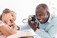 Young father with his cute little daughter taking pictures of each other on an old vintage camera stock image
