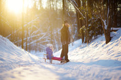 Young father and his daughter having fun with a sleight in beautiful winter park Stock Photos