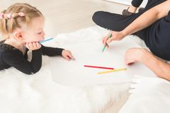 A young father and his daughter lie on the floor and draw with colored pencils. stock image