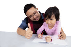 Young father and his daughter with thumb up. Photo of young father showing thumb up at the camera while helping her daughter to study Royalty Free Stock Photo