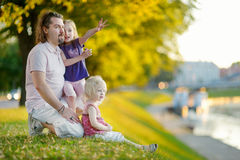 Young father and his daughters sitting by a river Stock Photo