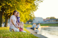 Young father and his daughters sitting by a river Stock Photography