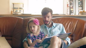 A young father and his happy little blond daughter are reading a story on leather sofa in the dining room. 4K stock video footage