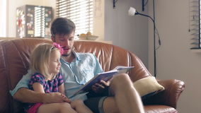 A young father and his happy little blond daughter are reading a story on leather sofa in the dining room. 4K stock video