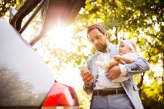 Young father with his little baby girl going into the car. Royalty Free Stock Photography