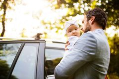 Young father with his little baby girl going into the car. Royalty Free Stock Photos