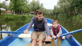 Young father and his little cute son sail on blue boat on lake among green trees. Happy daddy and son spend time together on lake. Happy father and son stock video footage
