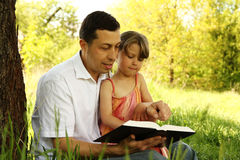 Young father with his little daughter reading the Bible Royalty Free Stock Photography