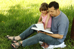 Young father with his little daughter reading the Bible Stock Images
