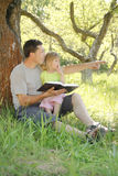 Young father with his little daughter reads the Bible Royalty Free Stock Photo
