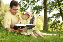 Young father with his little daughter reads the Bible Stock Photo