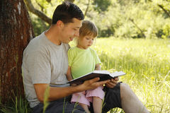 Young father with his little daughter reads the Bible Royalty Free Stock Image