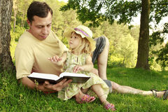 Young father with his little daughter reads the Bible Royalty Free Stock Photography