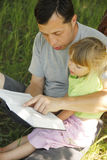Young father with his little daughter reads the Bible Stock Image